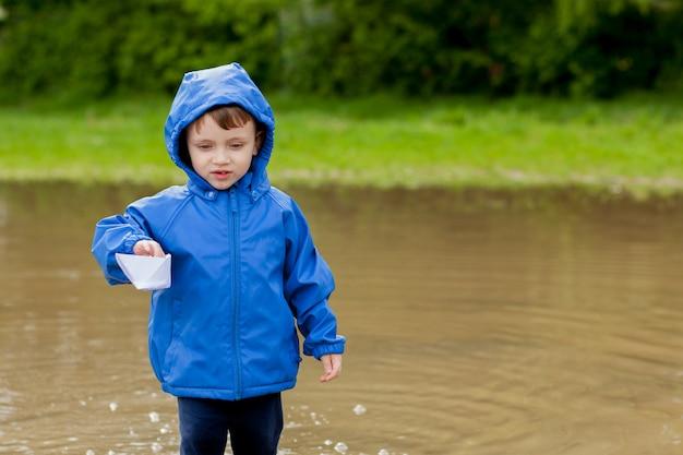 Kleiner junge, der mit handgemachtem schiff spielt