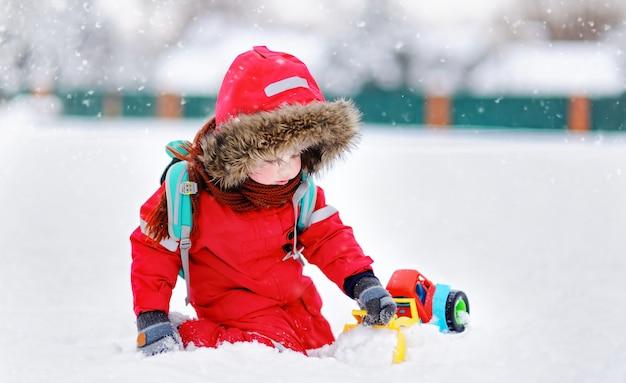 Kleiner junge, der mit hellem autospielzeug und frischem schnee spielt