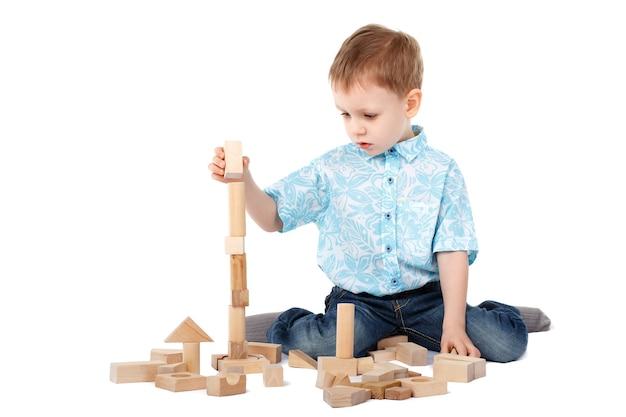 Kleiner junge, der mit hölzernem designer auf dem boden lokalisiert auf weißem hintergrund spielt