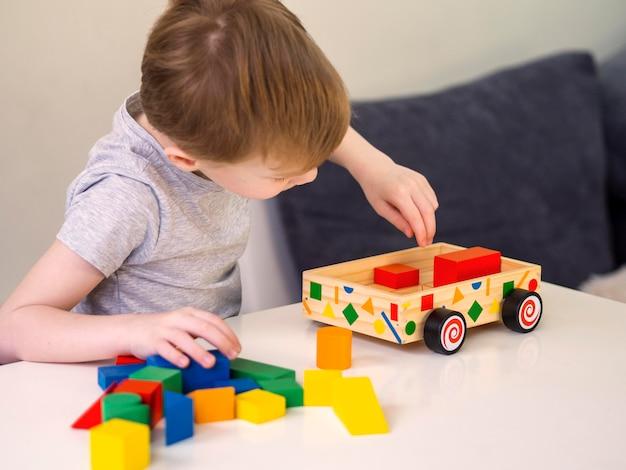 Kleiner junge, der mit interessantem hölzernem autospielzeug spielt