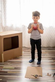 Kleiner junge, der mit karikaturbox spielt