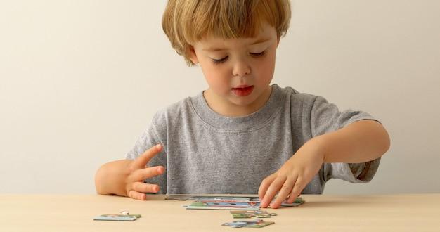 Kleiner junge, der mit puzzlespiel spielt