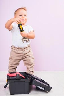 Kleiner junge, der mit schlüssel steht