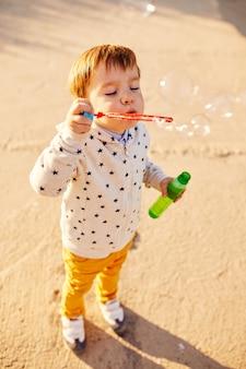 Kleiner junge, der mit seifenblasen spielt