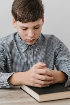 Kleiner junge, der mit seinen händen auf einer bibel betet