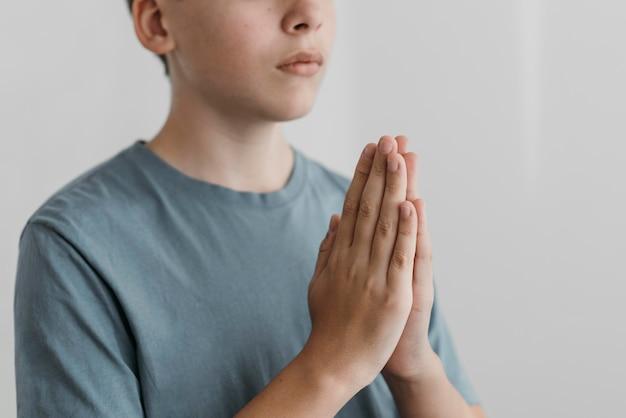 Kleiner junge, der mit seinen händen betet