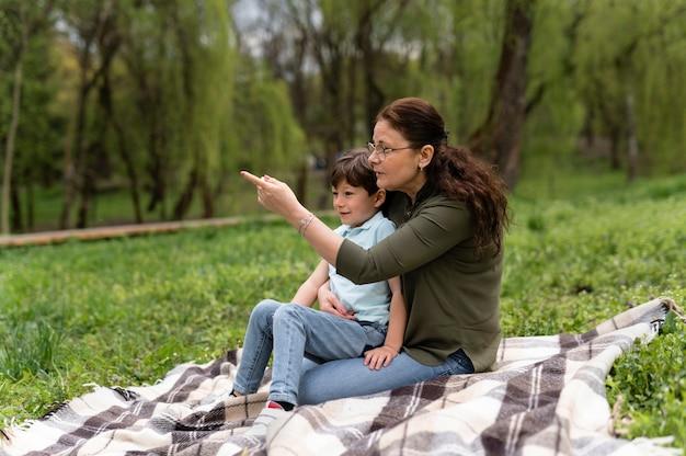 Kleiner junge, der mit seiner großmutter im park sitzt
