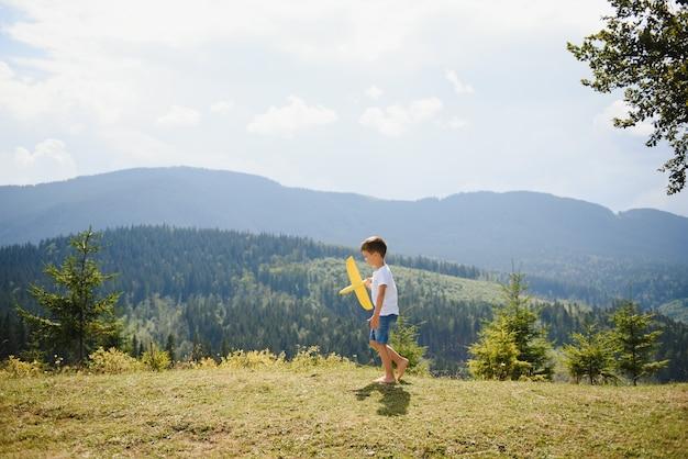 Kleiner junge, der mit spielzeugflugzeug spielt