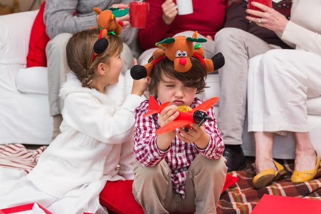 Kleiner junge, der mit spielzeugflugzeug während der weihnachtszeit spielt