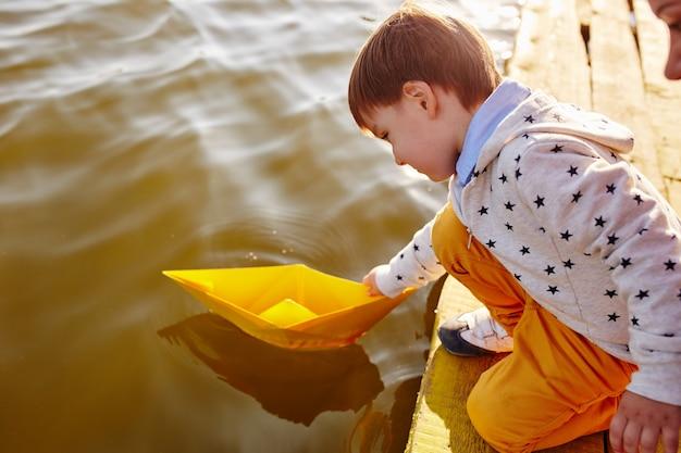 Kleiner junge, der mit spielzeugpapierschiff durch den see spielt