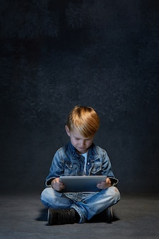 Kleiner junge, der mit tablette im studio sitzt