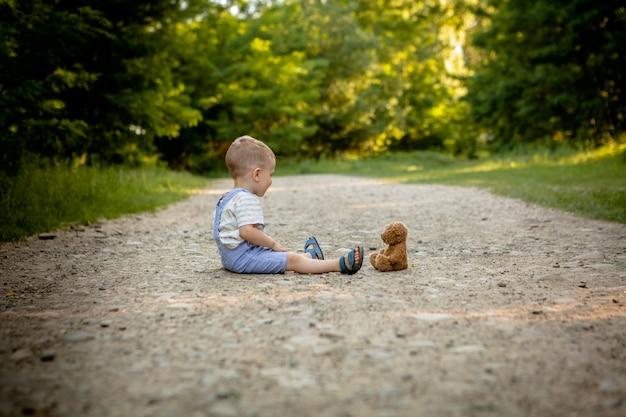 Kleiner junge, der mit teddybär auf dem fußweg spielt.