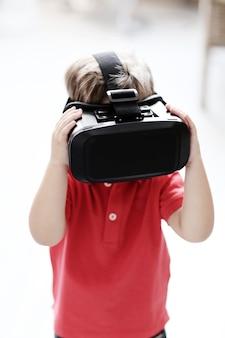 Kleiner junge, der mit virtueller realität unterhält