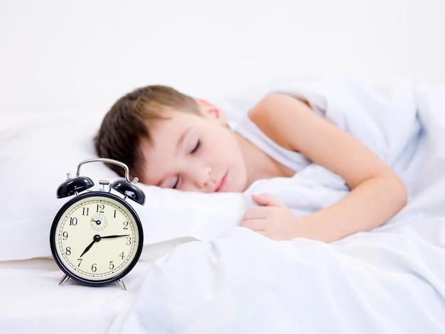 Kleiner junge, der mit wecker nahe seinem kopf schläft
