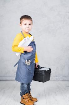 Kleiner junge, der mit werkzeugkasten- und papierrollen steht