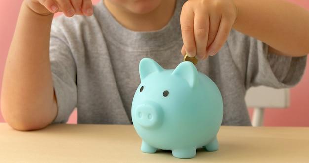 Kleiner junge, der münzen in ein sparschwein einsetzt