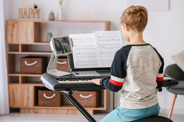 Kleiner junge, der musik mit seinem freund online zu hause studiert