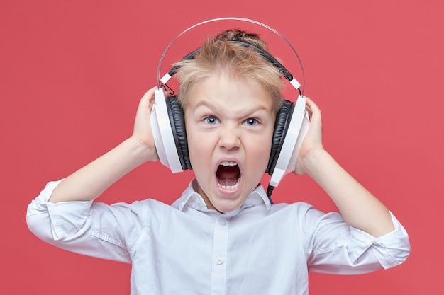 Kleiner junge, der musik über kopfhörer hört und schreit