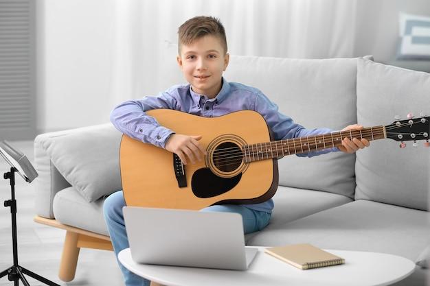 Kleiner junge, der musikunterricht online zu hause nimmt