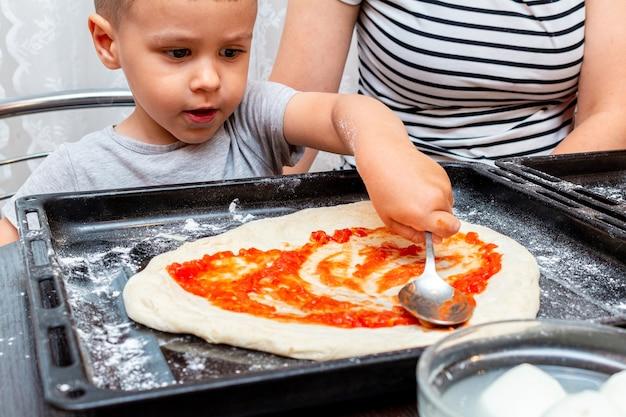 Kleiner junge, der mutter hilft, macht pizza zu hause