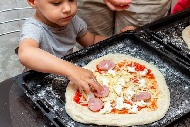 Kleiner junge, der mutter hilft, pizza zu hause zu machen