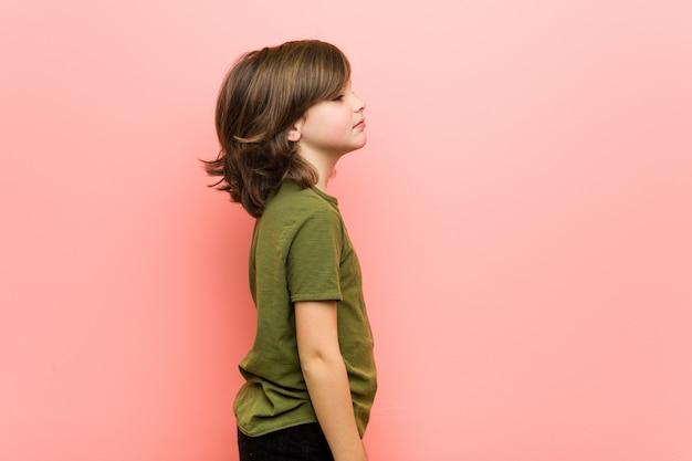 Kleiner junge, der nach links, seitwärts haltung anstarrt.