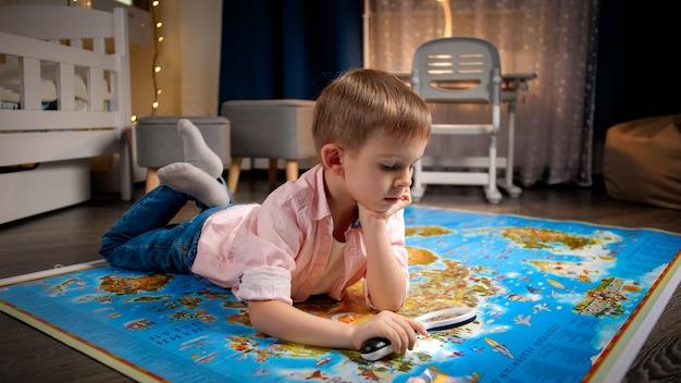 Kleiner junge, der nachts auf dem boden liegt und große weltkarte erforscht. konzept von reisen, tourismus und kindererziehung. erkundungen und entdeckungen für kinder.