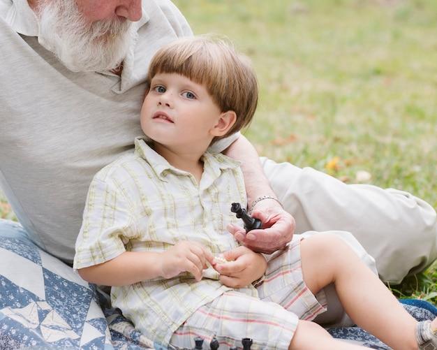 Kleiner junge der nahaufnahme mit dem großvater, der kamera betrachtet