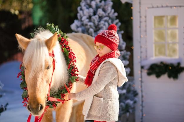 Kleiner junge der nahaufnahme mit gläsern und entzückend nahe dem kleinen holzhaus und den schneebedeckten bäumen.