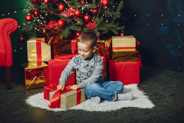 Kleiner junge, der nahe weihnachtsbaum sitzt