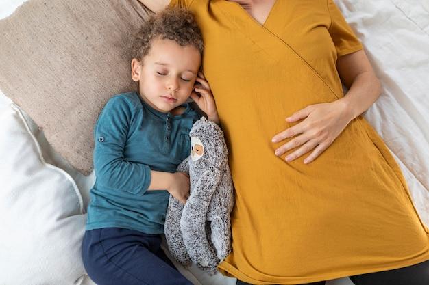 Kleiner junge, der neben seiner mutter schläft