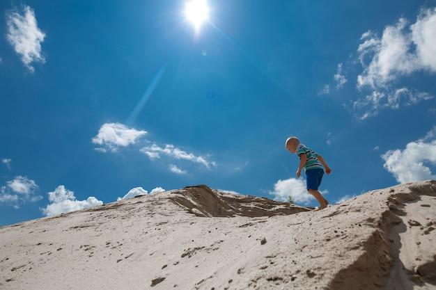 Kleiner junge, der oben auf einem sandigen hügel im hintergrund des blauen himmels klettert