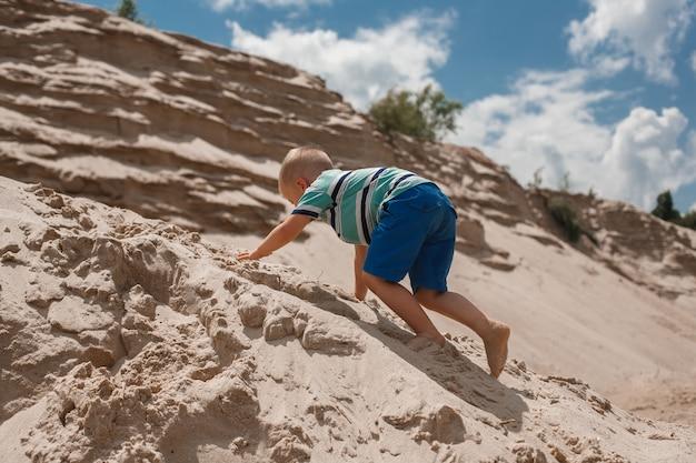 Kleiner junge, der oben auf einer sandigen hügelrückseitenansicht klettert.