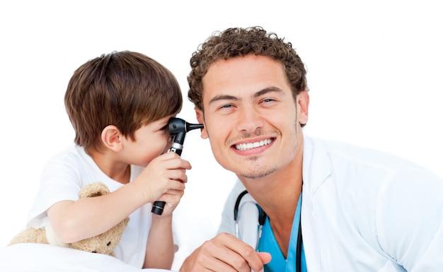 Kleiner junge, der ohren doktors überprüft