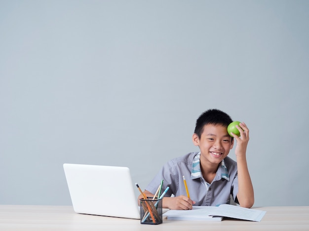 Kleiner junge, der online mit laptop lernt. fernunterricht während der covid-19-pandemie