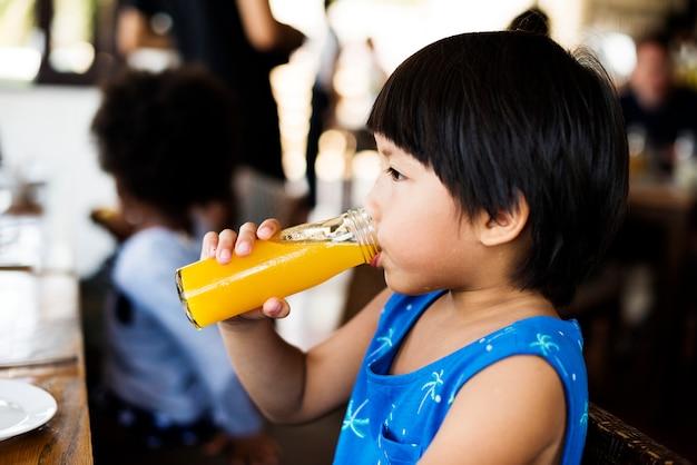 Kleiner junge, der orangensaft trinkt