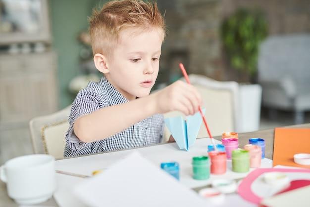 Kleiner junge, der papierebene malt