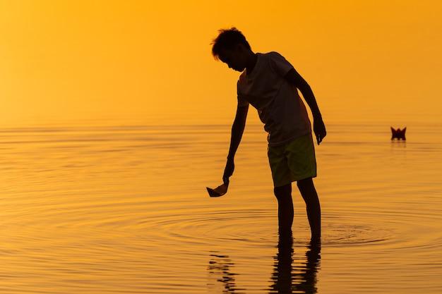 Kleiner junge, der papierschiffe vom flussufer startet. schwimmende schiffe in die ferne