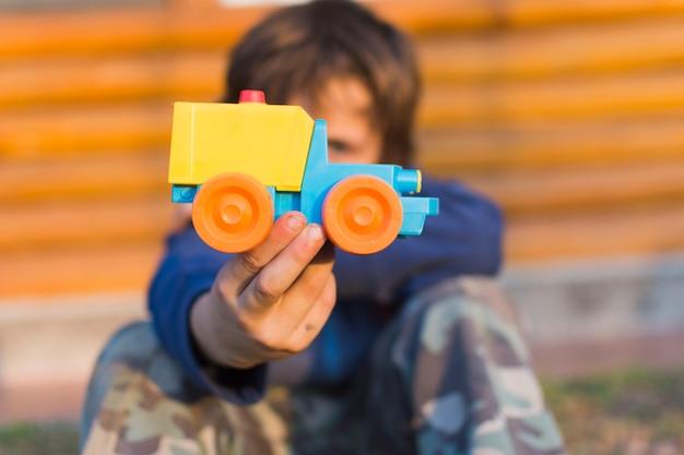 Kleiner junge, der plastikspielzeugauto hält