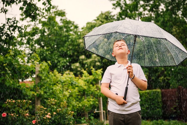 Kleiner junge, der regenschirm hält und auf dem regen steht