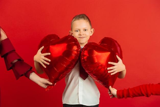 Kleiner junge, der rote herzförmige luftballons hält