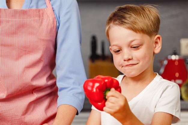 Kleiner junge, der rote paprika in der küche hält