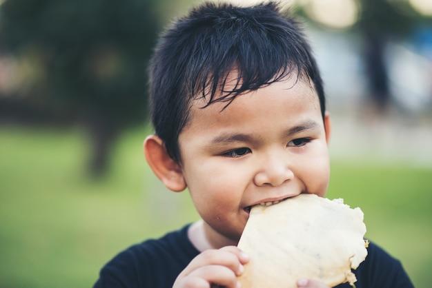 Kleiner junge, der sandwich des frischen brötchens des lebensmittels isst