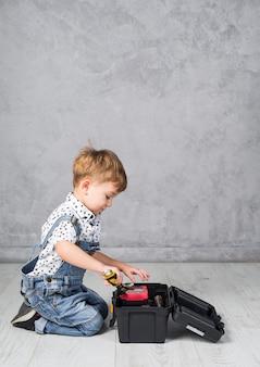 Kleiner junge, der schlüssel in werkzeugkasten einsetzt