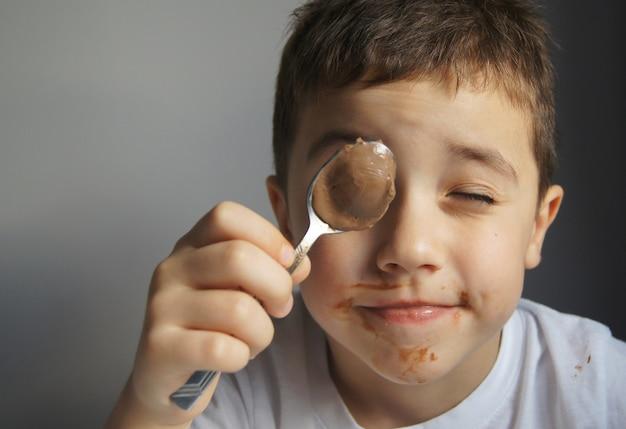 Kleiner junge, der schokolade durch löffel isst. graue wand. nettes glückliches kind bedeckt durch schokolade