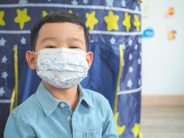 Kleiner junge, der schutzmaskenschutz vor virus oder kranken leuten trägt