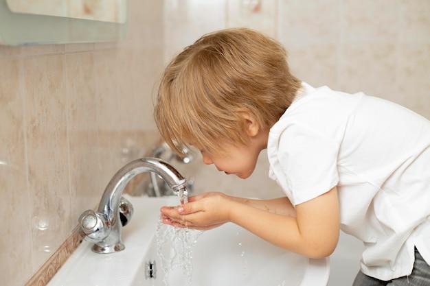 Kleiner junge, der sein gesicht wäscht