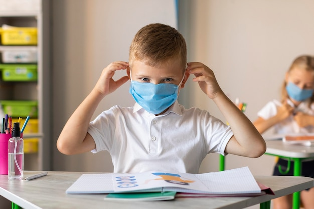 Kleiner junge, der seine medizinische maske aufsetzt