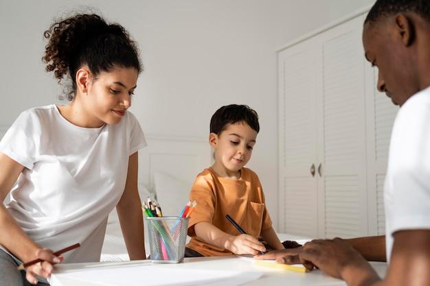 Kleiner junge, der seine vaterhand auf papier zeichnet