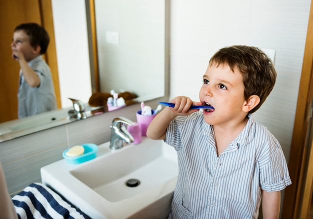 Kleiner junge, der seine zähne allein putzt